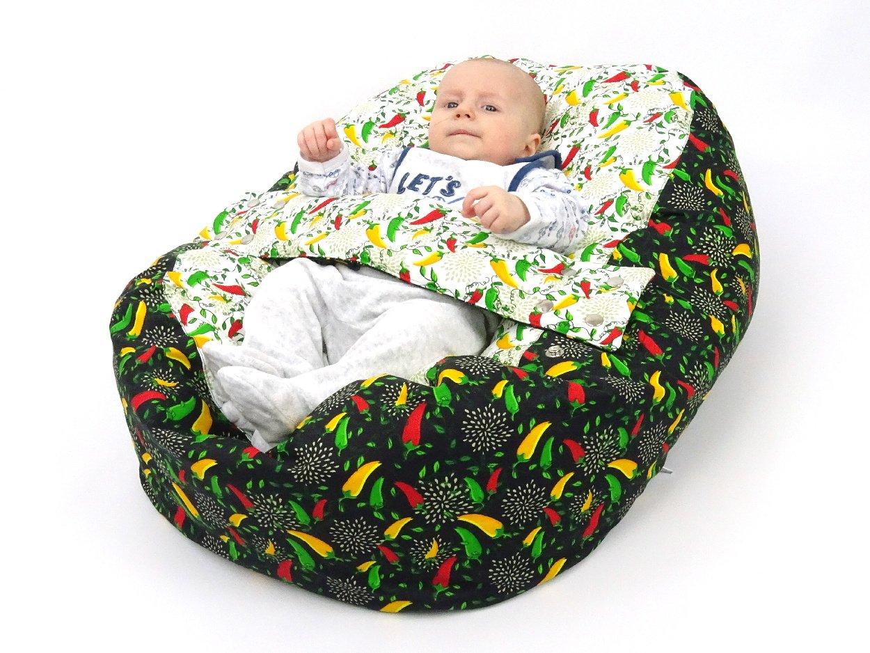 Baby im Liegekissen mit Chillischoten Muster